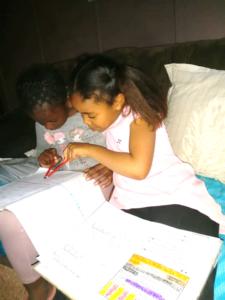 Ora helping her friend, Thandi, with homework